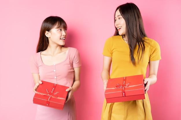 Portret dwóch pięknych młodych azjatek trzymających czerwone pudełko na różowej ścianie