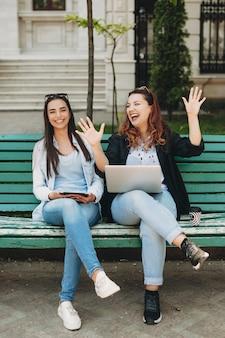 Portret dwóch pięknych młodych kobiet, zabawy, podczas gdy jeden pokazuje coś ręką, a inny śmieje się patrząc na kamery, siedząc na plaży.