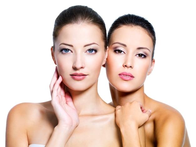 Portret dwóch pięknych seksownych młodych kobiet na białym tle