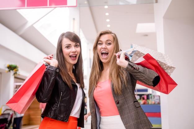 Portret dwóch podekscytowanych kobiet z torby na zakupy