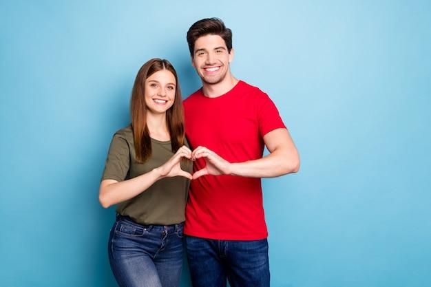 Portret dwóch pozytywnych małżonków pokazuje kształt serca ręce namiętna miłość symbol świętować walentynki wakacje nosić zielony nowoczesny t-shirt dżinsowy strój na białym tle niebieski kolor tło