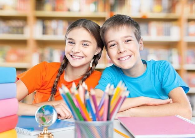 Portret dwóch pracowitych dziewczyn patrzących na kamerę w miejscu pracy z uczniami na tle