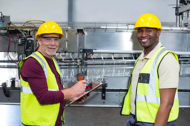 Portret dwóch pracowników fabrycznych ze schowka stojący obok linii produkcyjnej