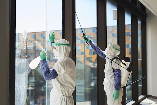 Portret dwóch pracowników ubranych w kombinezony ochronne do dezynfekcji okien biurowych w świetle słonecznym,