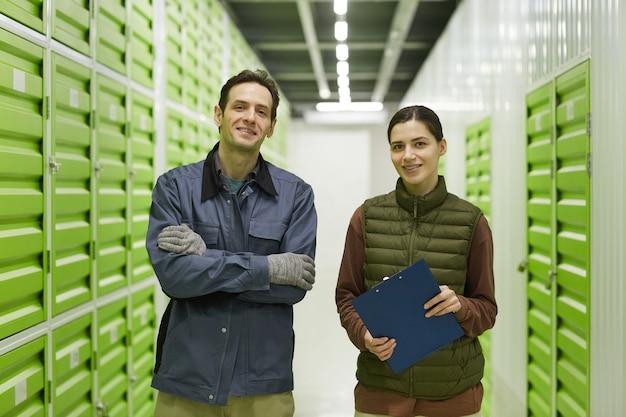 Portret dwóch pracowników uśmiechających się do kamery stojąc w magazynie