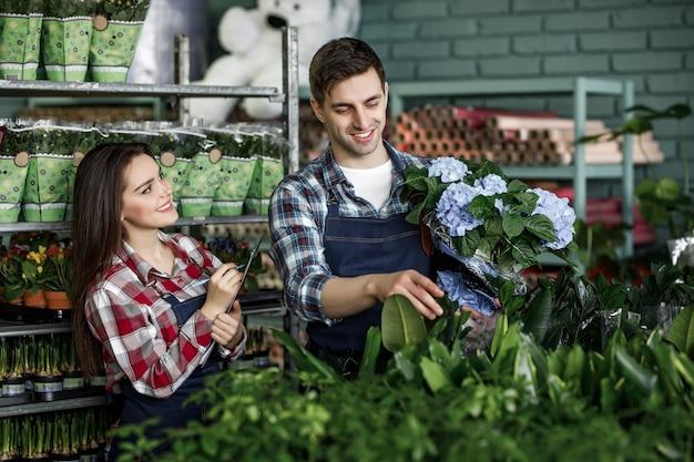 Portret dwóch pracowników w specjalnych ubraniach pracujących w szklarni w centrum ogrodniczym