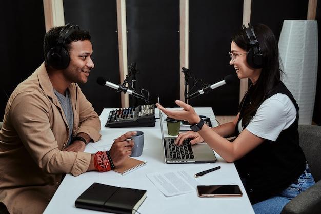 Portret dwóch prezenterów radiowych, młodego mężczyzny i kobiety, rozmawiających ze sobą podczas moderowania programu na żywo