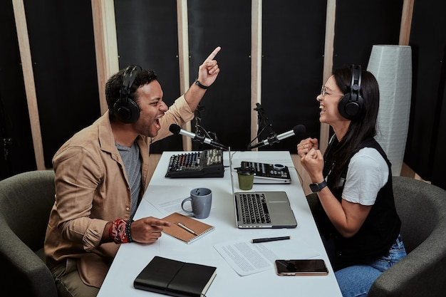 Portret dwóch prezenterów radiowych, młodego mężczyzny i kobiety, wyglądających emocjonalnie podczas rozmowy ze sobą