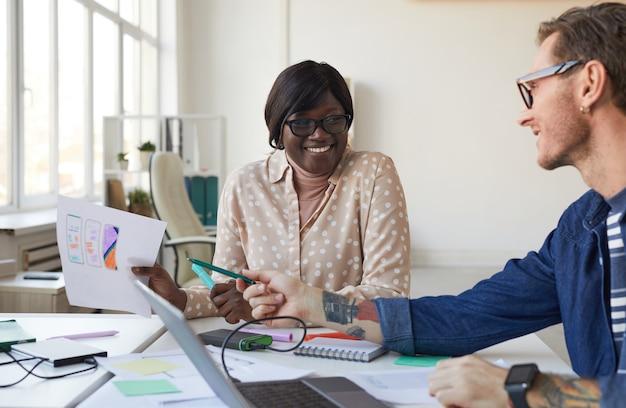 Portret dwóch programistów it uśmiechniętych podczas projektowania interfejsu aplikacji mobilnej lub strony internetowej, kopia przestrzeń