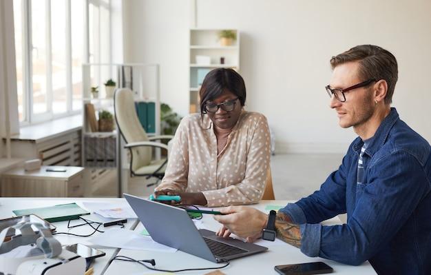Portret dwóch programistów it wskazujących na ekran laptopa podczas współpracy nad aplikacją mobilną lub projektowaniem stron internetowych, kopia miejsca
