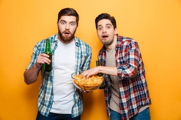 Portret dwóch przestraszonych młodych mężczyzn pije piwo