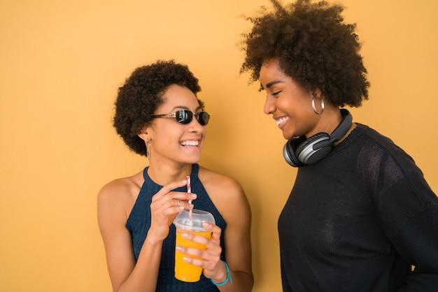 Portret dwóch przyjaciół afro, którzy razem bawią się i cieszą się dobrym czasem przy piciu świeżych soków owocowych. koncepcja przyjaźni i stylu życia.