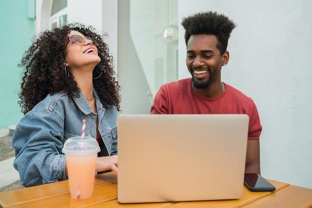 Portret dwóch przyjaciół afro za pomocą laptopa podczas picia świeżego soku owocowego na zewnątrz w stołówce.