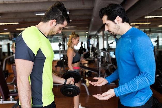Portret dwóch przystojnych młodych mężczyzn robi ćwiczenia mięśni w siłowni.