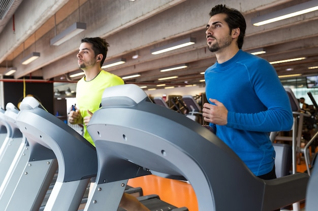 Portret dwóch przystojnych młodych mężczyzn robi treningu cardio w siłowni.