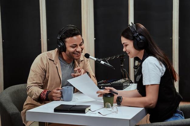 Portret dwóch radiowców, mężczyzny i kobiety, rozmawiających ze sobą, czytających scenariusz podczas pobierania