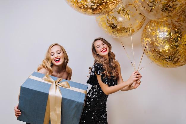 Portret dwóch radosnych podekscytowanych wspaniałych kobiet z długimi kręconymi włosami świętującymi urodziny na białej przestrzeni. duży prezent, balony ze złotymi świecidełkami,