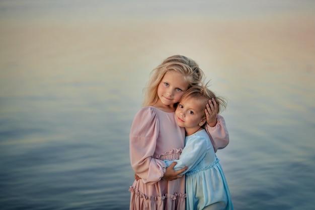 Portret dwóch sióstr szczęśliwych ślicznych dziewcząt w delikatnych pięknych sukienkach. wybrzeże, lato i zachód słońca.