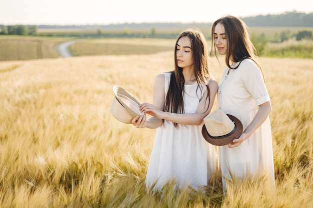 Portret dwóch sióstr w białych sukienkach z długimi włosami na polu
