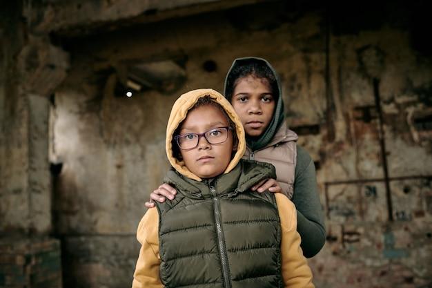 Portret dwóch sióstr w bluzach stojących w opuszczonym domu, które zostawiły same po działaniach wojennych