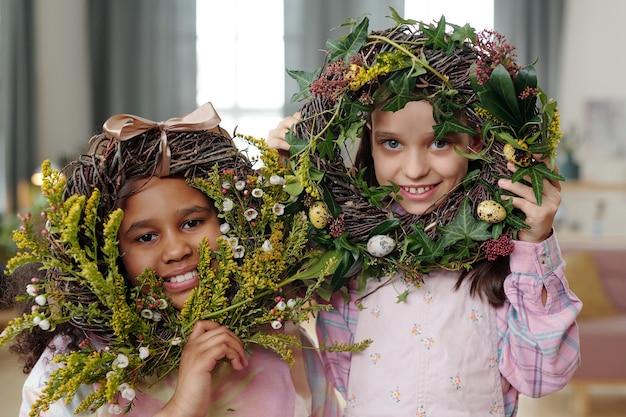Portret dwóch ślicznych małych dziewczynek uśmiechających się do kamery, pozujących razem z wielkanocnym wieńcem kwiatowym