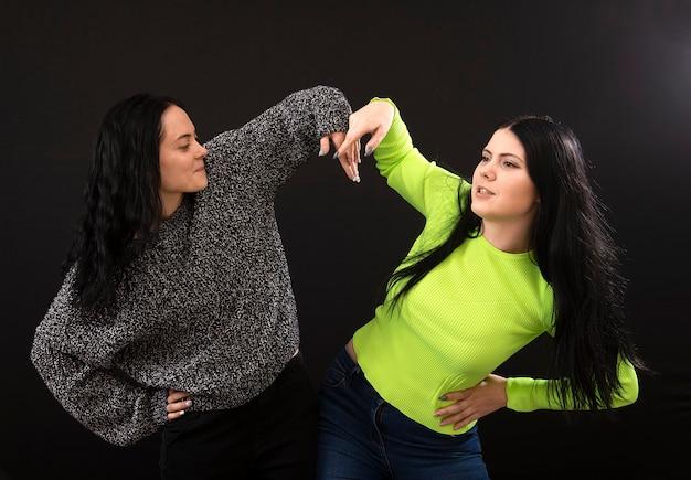 Portret dwóch śmiesznych kobiet w ubranie, uśmiechając się i gestykulując znak ok na białym tle