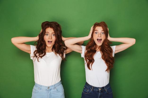 Portret dwóch śmiesznych kobiet z rudymi włosami w białych koszulkach patrząc na kamery i obejmujących uszy na białym tle na zielonym tle