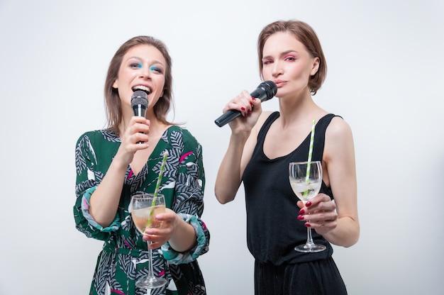 Portret dwóch śpiewających dziewcząt w okularach w dłoniach. koncepcja karaoke. różne środki przekazu