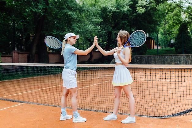 Portret dwóch sportowych dziewcząt tenisistek z rakietami zakończonych zawodów.