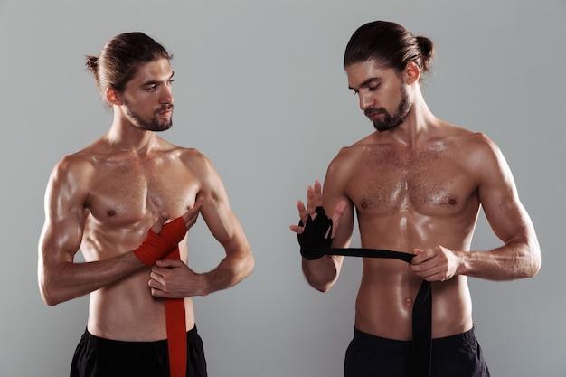 Portret dwóch sportowych, muskularnych, bez koszuli braci bliźniaków