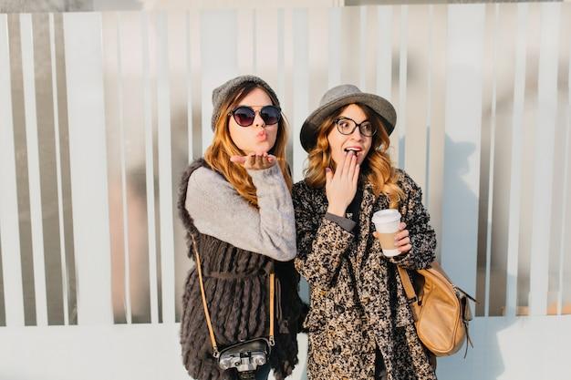 Portret dwóch stylowych zabawnych szczęśliwych kobiet, zabawy na ulicy w mieście. słoneczny dzień modnej młodej kobiety podróżującej razem, wyrażającej pozytywne nastawienie, prawdziwe emocje, figlarnej, cieszącej się słońcem, uśmiechającej się.