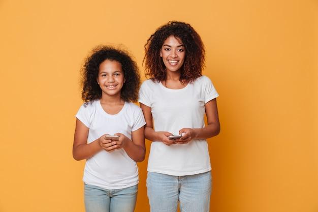 Portret dwóch szczęśliwych afro amerykańskich sióstr ze smartfonami