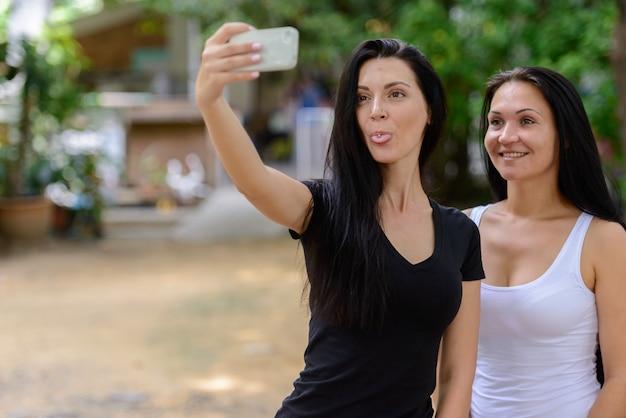 Portret dwóch szczęśliwych pięknych kobiet razem na zewnątrz biorąc selfie