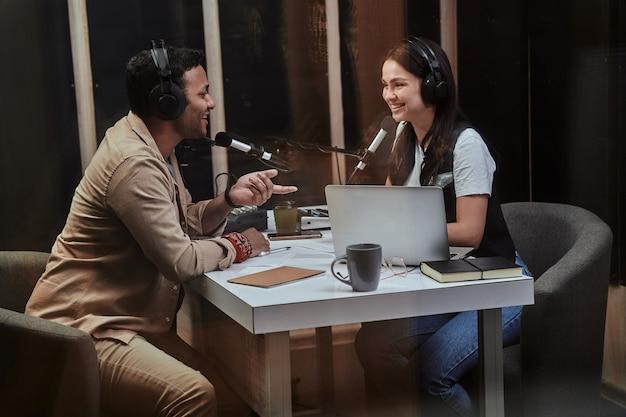 Portret dwóch szczęśliwych prezenterów radiowych, młodego mężczyzny i kobiety, uśmiechnięci podczas dyskusji na różne tematy