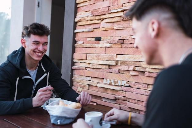 Portret dwóch szczęśliwych przyjaciół picia kawy w barze.