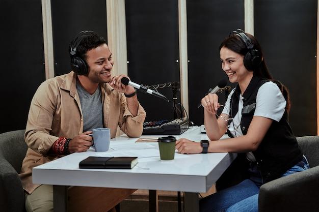Portret dwóch szczęśliwych radiowców, mężczyzny i kobiety, uśmiechniętych podczas rozmowy, moderujących a