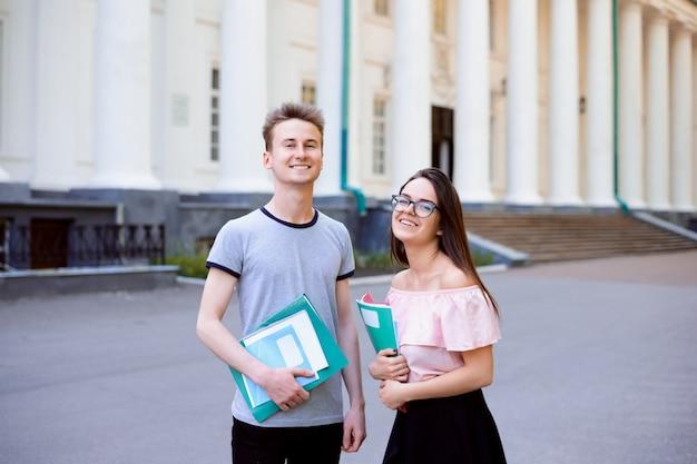 Portret dwóch szczęśliwych studentów stojących przed uniwersytetem przed zajęciami