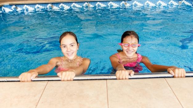 Portret dwóch szczęśliwych, wesołych uśmiechniętych nastoletnich dziewcząt na krytym basenie