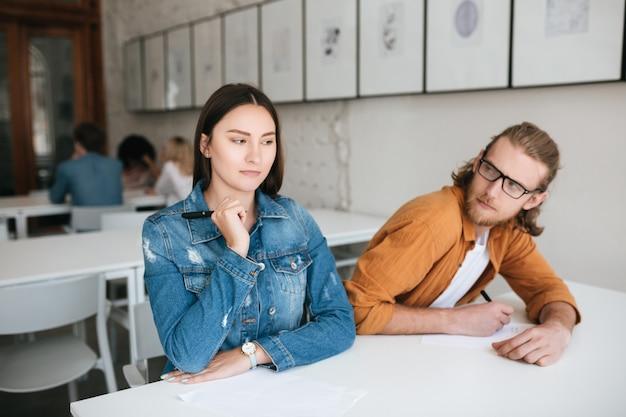 Portret dwóch uczniów siedzących przy biurku w klasie i pisania testu