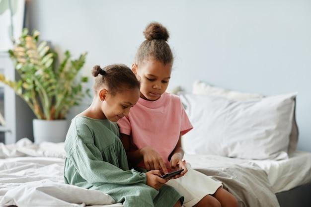 Portret dwóch uroczych afrykańskich dziewczyn używających smartfona razem siedząc na łóżku w przytulnym pokoju...