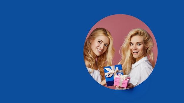 Portret dwóch uroczych bliźniaczek womanfriens kobiet trzymających prezenty i pudełka zerkające przez niebieską dziurę w ścianie. opróżnia przestrzeń dla teksta ,.
