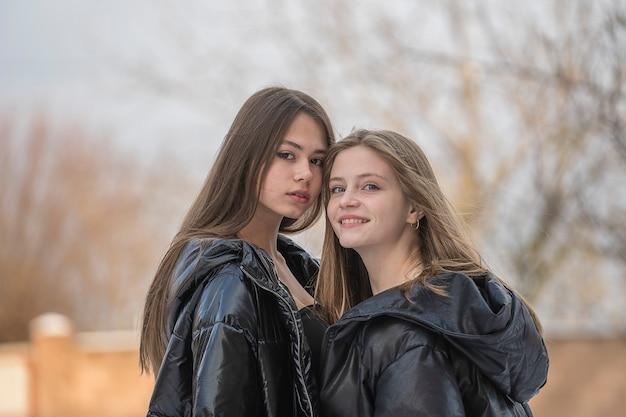 Portret dwóch uroczych młodych dziewcząt, na zewnątrz, z bliska. szczęśliwa młoda para dziewcząt razem na zaśnieżonej ulicy podczas zimy