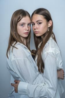 Portret dwóch uroczych młodych dziewcząt, w pomieszczeniu, z bliska