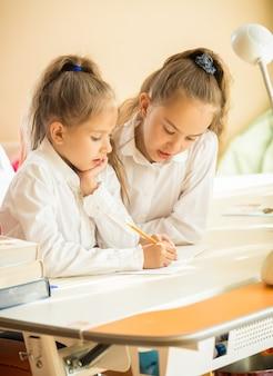 Portret dwóch uroczych uczennic piszących w podręczniku przy biurku