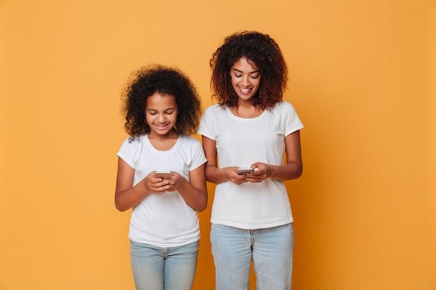 Portret dwóch uśmiechniętych afro amerykańskich sióstr ze smartfonów