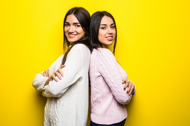 Portret dwóch uśmiechniętych dziewcząt ubranych w swetry stojących tyłem do siebie na białym tle nad żółtą ścianą