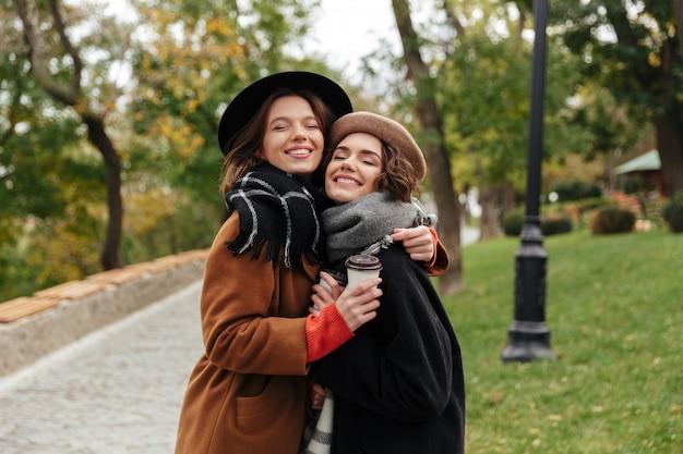 Portret dwóch uśmiechniętych dziewcząt ubranych w ubrania jesienią przytulanie