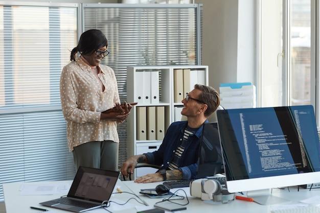 Portret dwóch uśmiechniętych informatyków omawiających projekty podczas pracy nad grami vr i oprogramowaniem w biurze, kopia przestrzeń