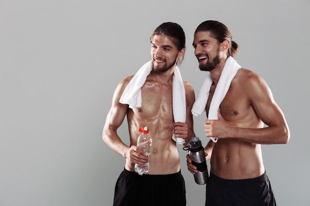 Portret dwóch uśmiechniętych, muskularnych, bez koszuli braci bliźniaków