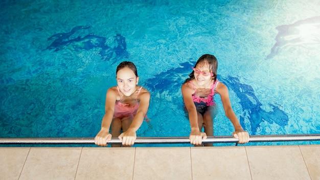 Portret dwóch uśmiechniętych nastoletnich dziewcząt pływających w basenie na siłowni